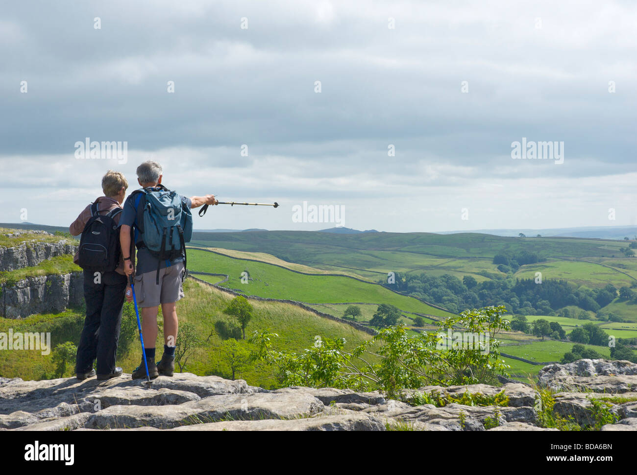 Two people enjoying the view from the top of Malham Cove, Yorkshire Dales National Park, North Yorkshire,  England Stock Photo