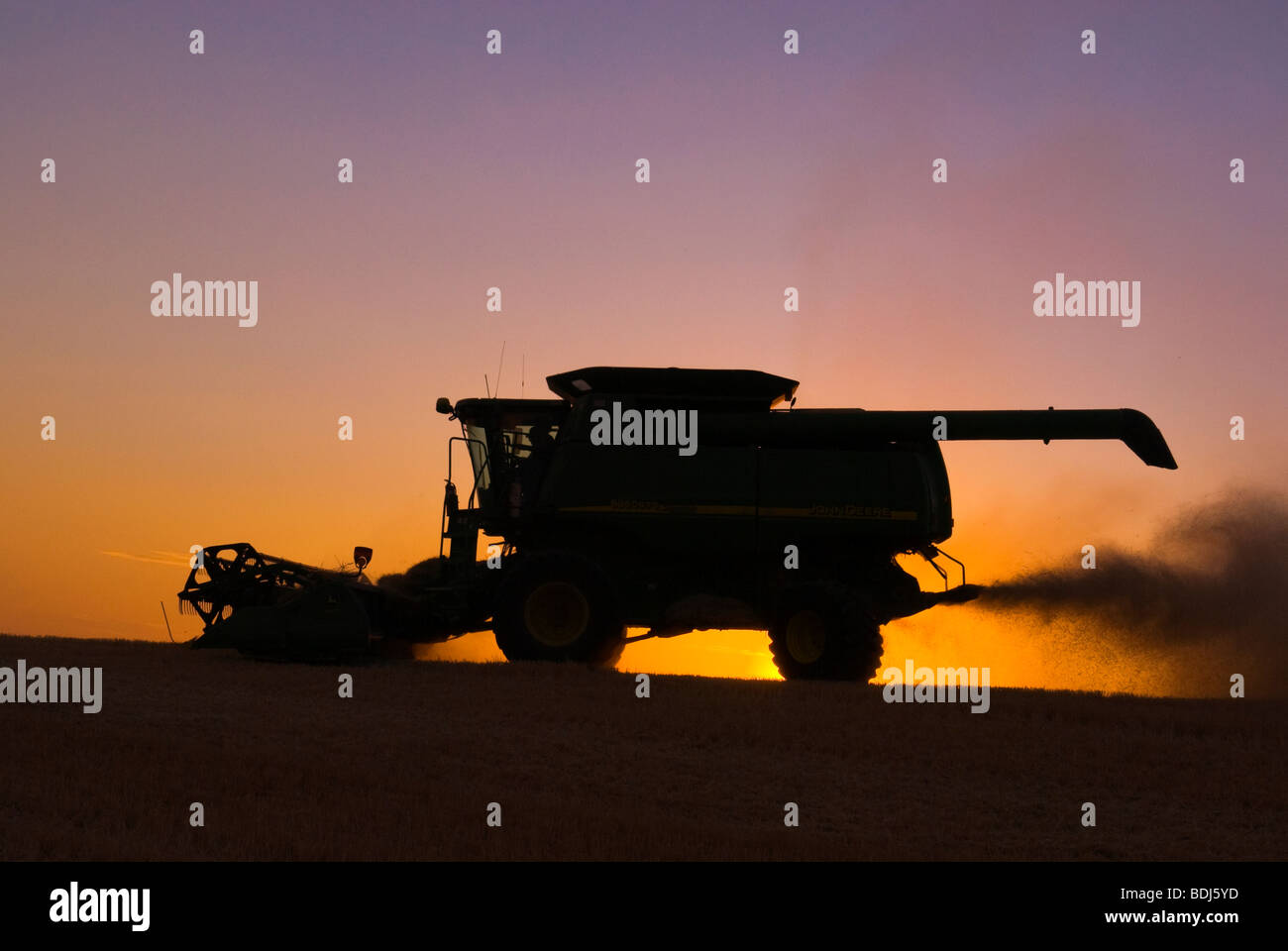 Agriculture - A John Deere combine, silhouetted by the sunset, harvests barley / Palouse Region, near Pullman, Washington, - Stock Image