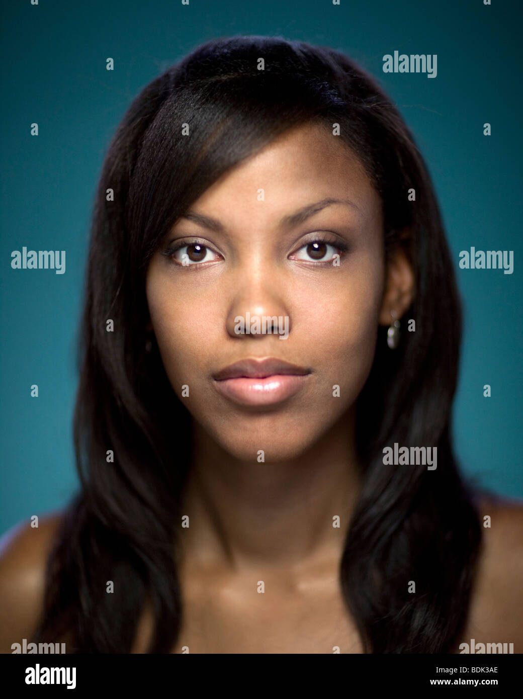 Close up portrait of African woman on blue background. - Stock Image