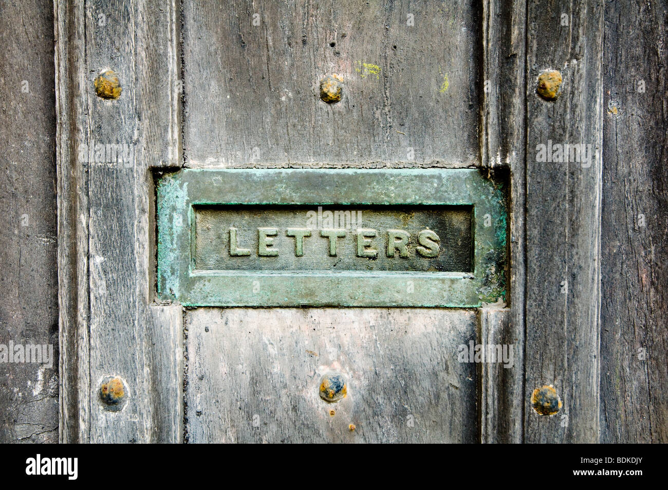 A letter box, with a verdigris patina, inset into an old and weathered oak door, with heavy nails. Stock Photo