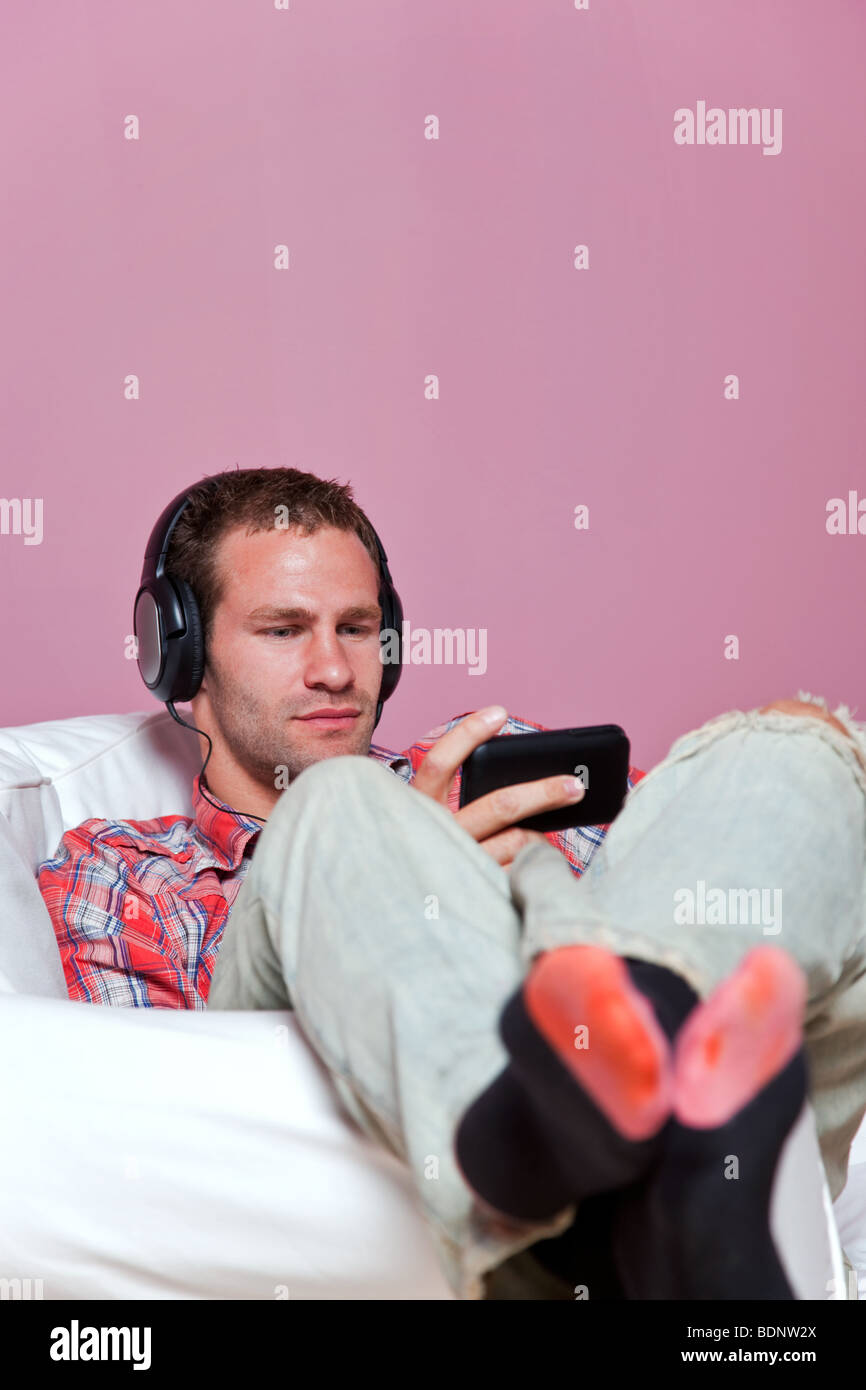 Relaxed male sitting listening to music on his mp3 player - Stock Image