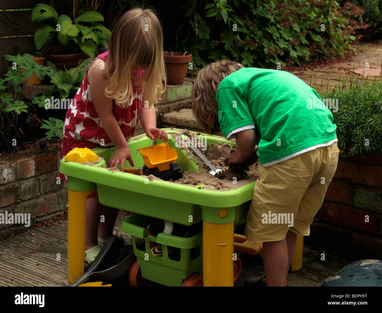 Brother and Sister Playing with sand in Back Garden Birmingham West Midlands Stock Photo