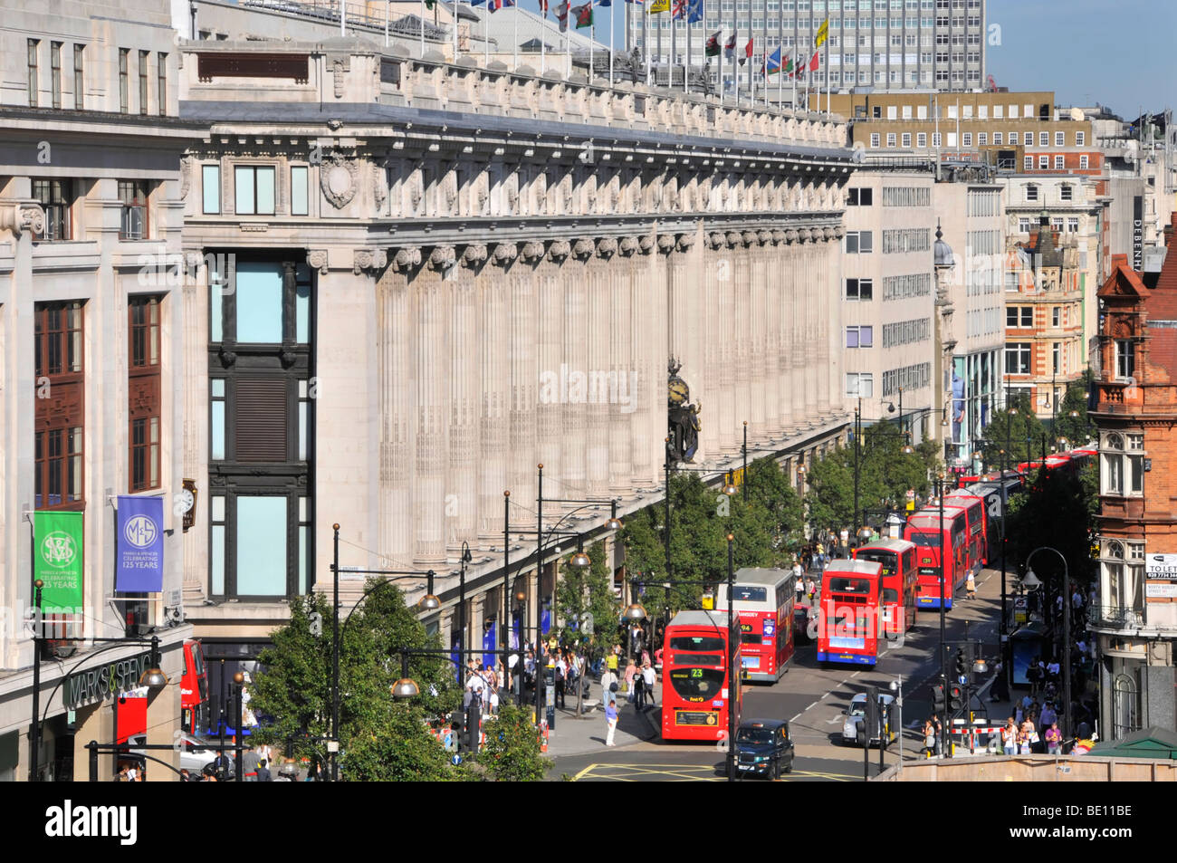 Oxford Street frontage of Selfridges department store with long queue of double decker red London buses Stock Photo
