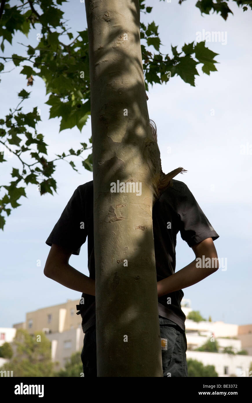 youth hiding behind a tree trunk - Stock Image
