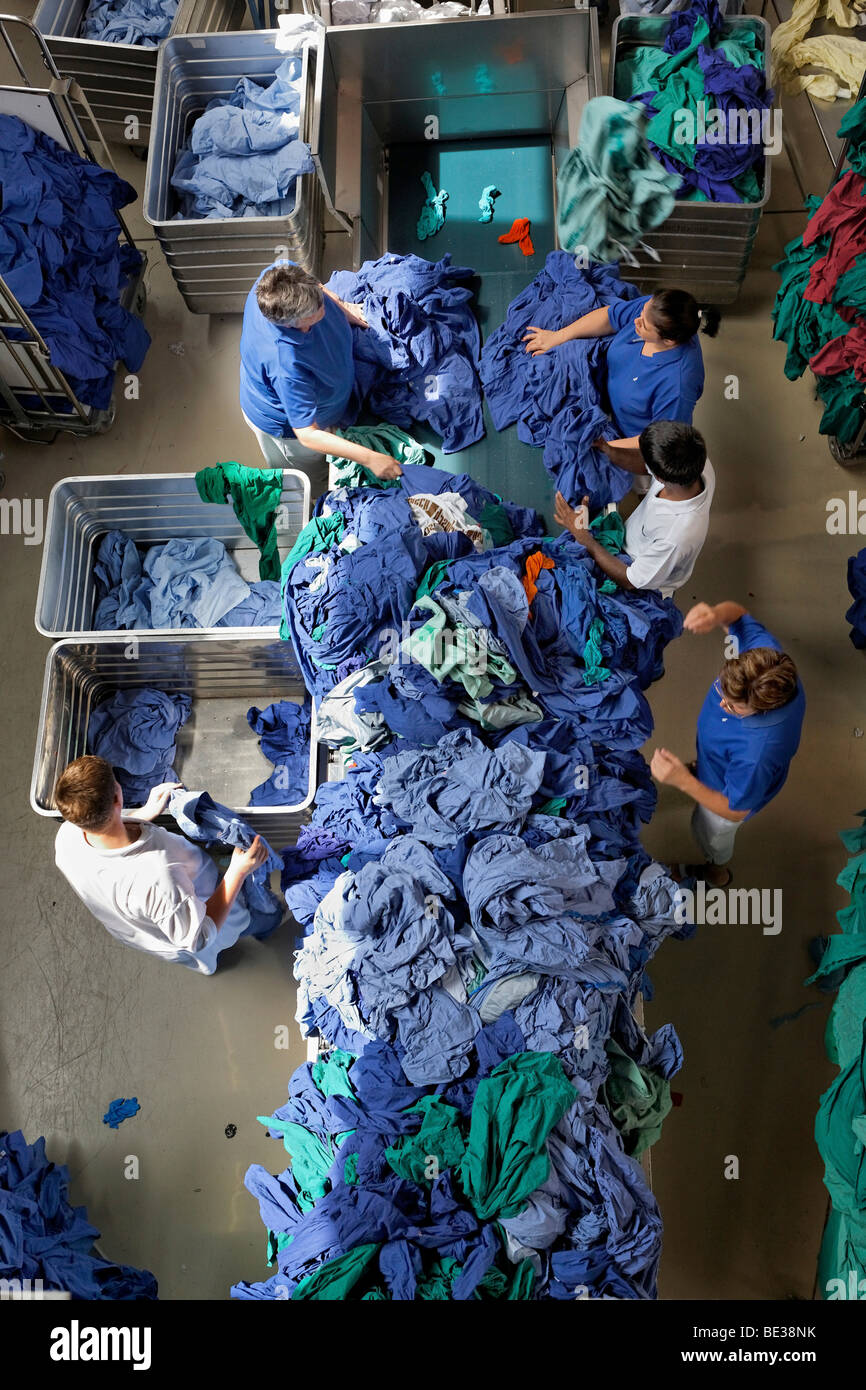 Green and blue hospital clothes being sorted by type and colour after being washed in an industrial laundry, Textil - Stock Image