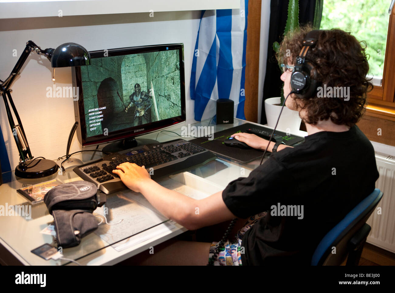 A boy, about 15, playing a violent game on the computer in his room, Germany, Europe - Stock Image