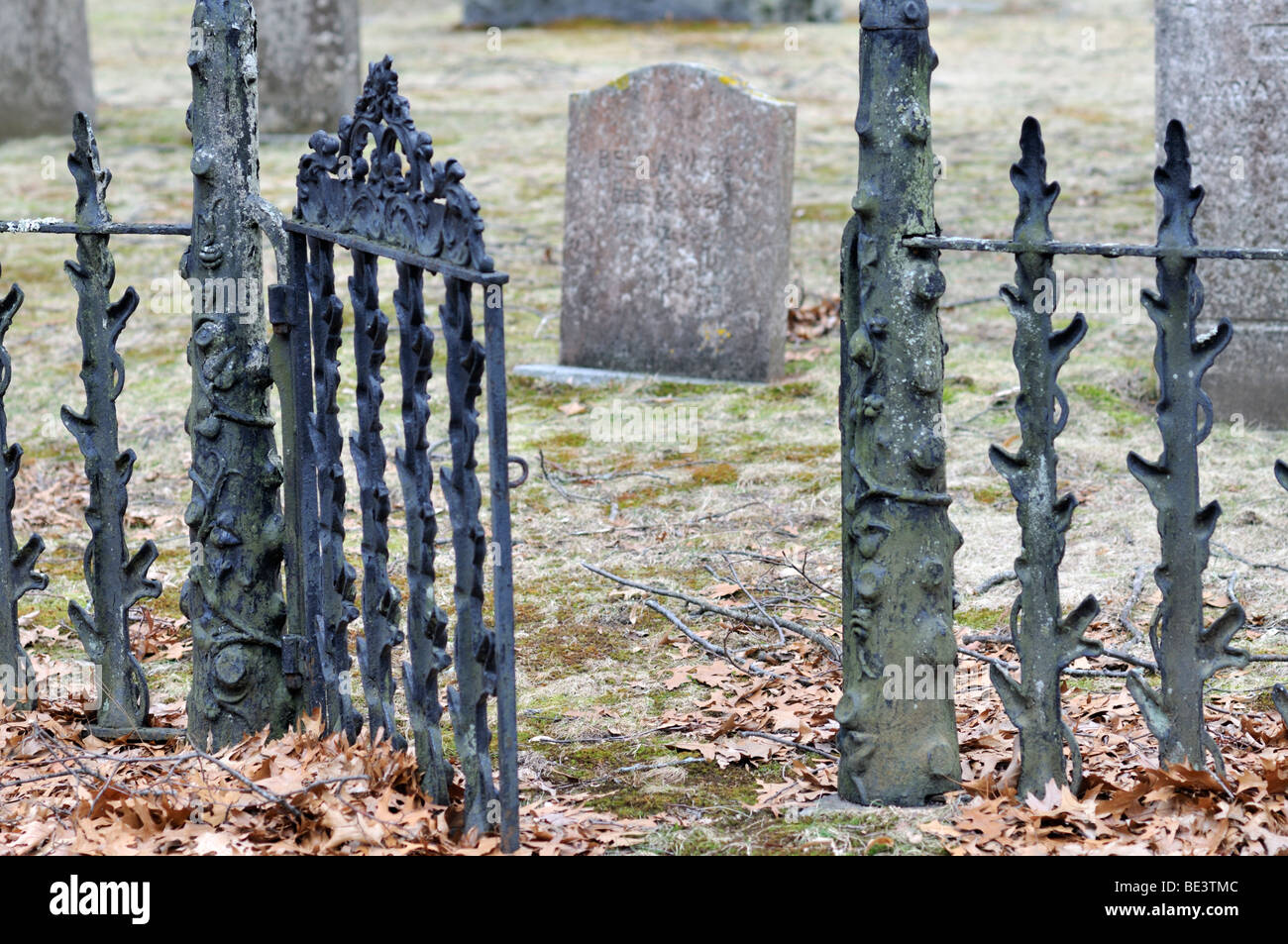 wrought iron gate open to old cemetery grave plot and gravestones