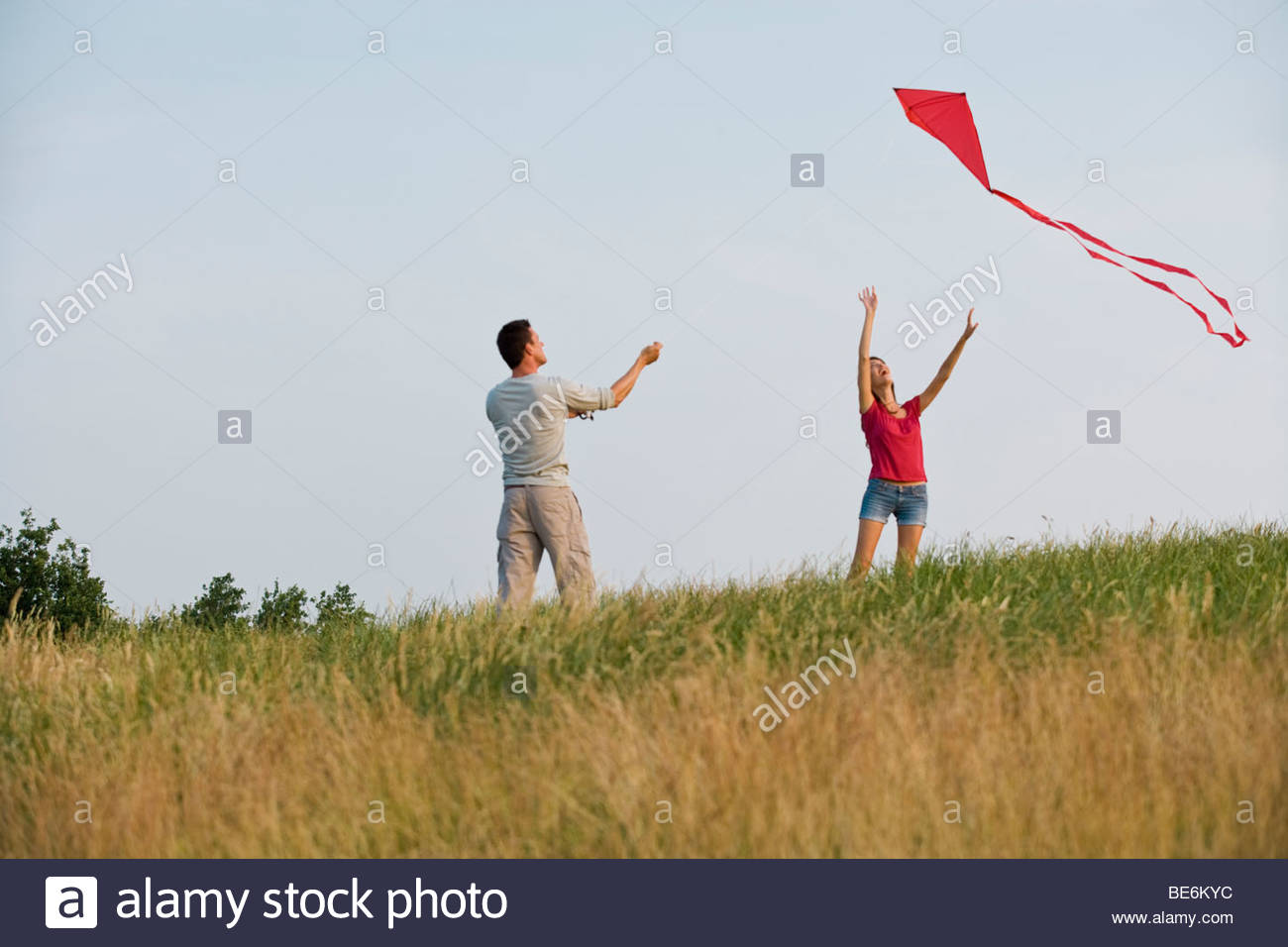 A young couple flying a red kite - Stock Image