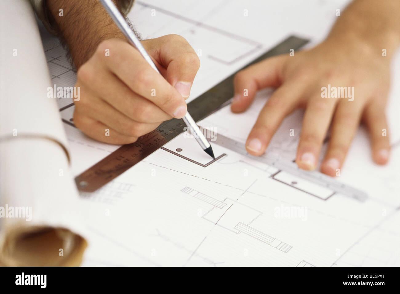 Architect editing blueprint, close-up - Stock Image