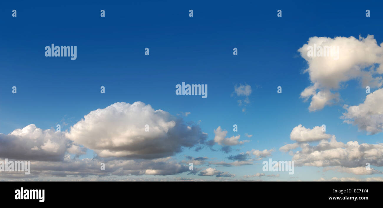 Blue sky with fluffy clouds in sunshine day, panoramic picture - Stock Image
