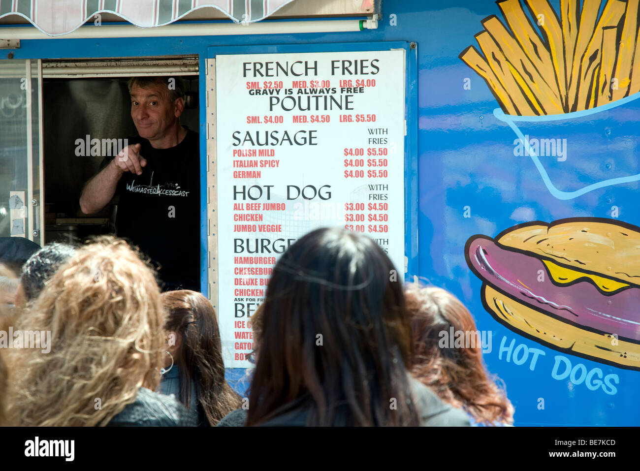 The owner of Mr. Tasty Fries - also known as 'The Blue Chip Truck' - taking fast food orders outside of - Stock Image