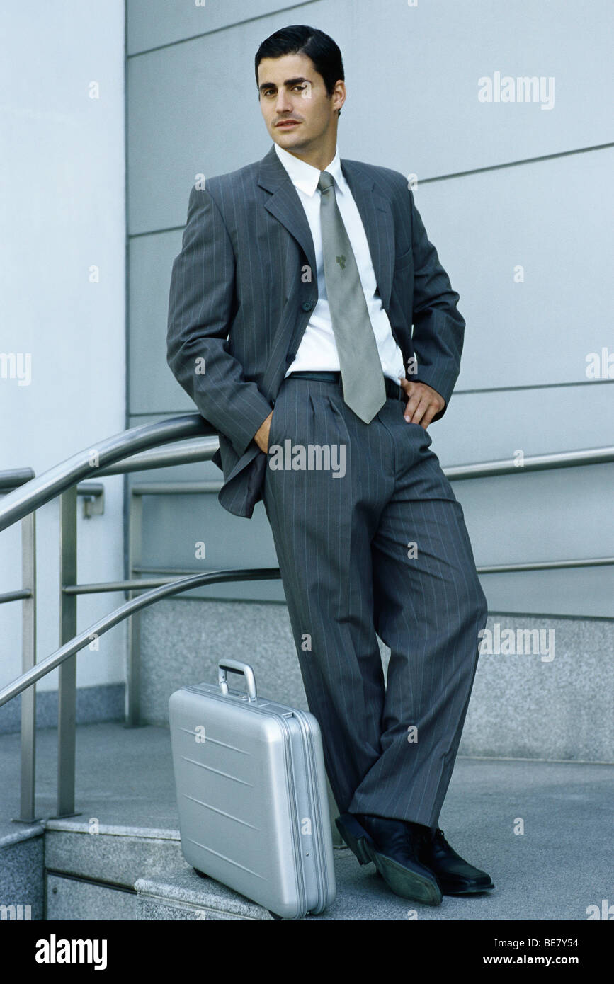 Businessman leaning against railing, briefcase on sidewalk at feet - Stock Image
