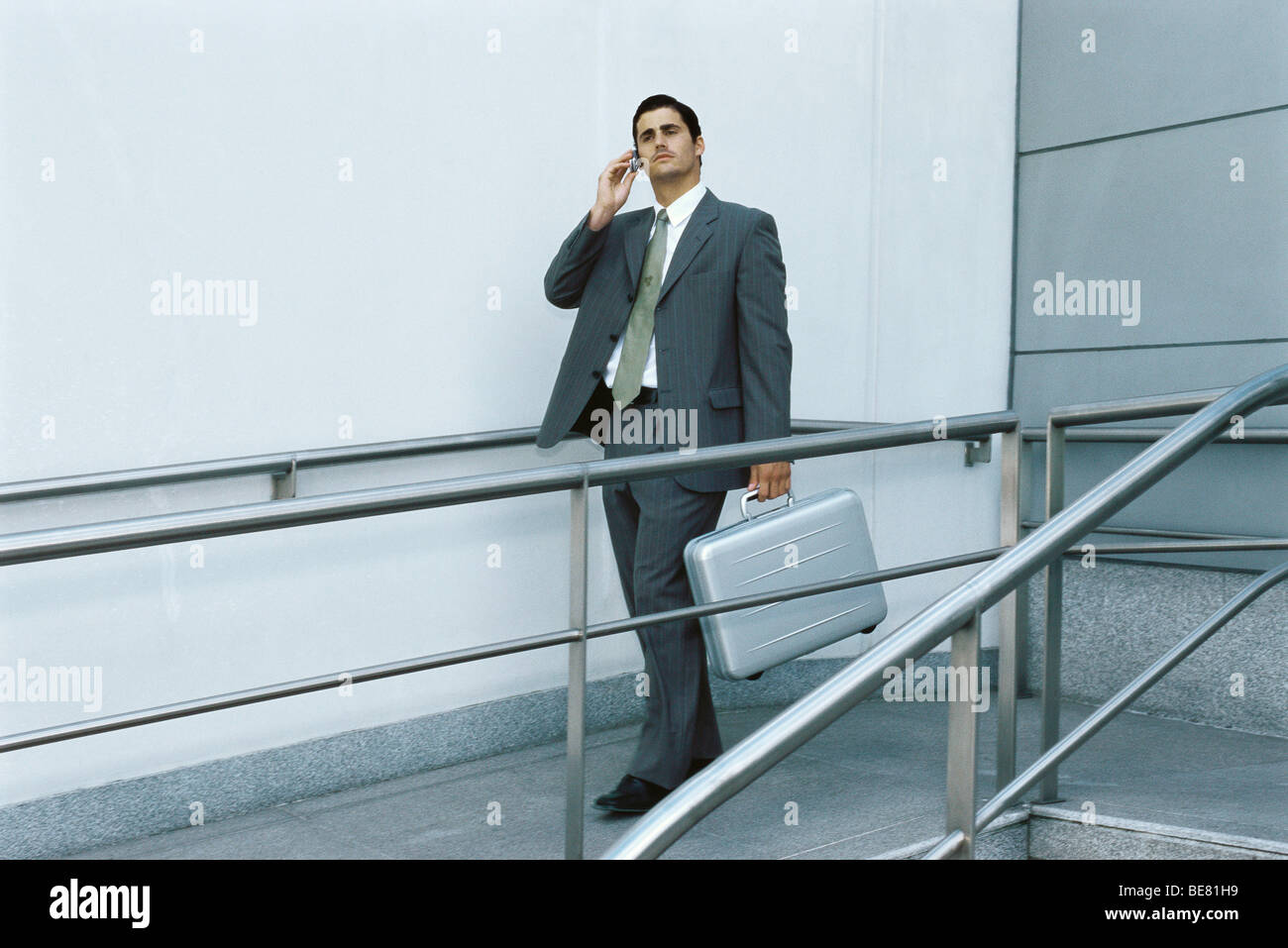 Businessman walking on sidewalk using cell phone, carrying briefcase - Stock Image