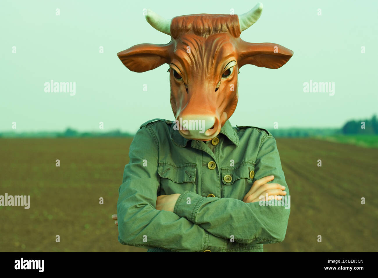 Person wearing bull mask, arms folded across chest - Stock Image
