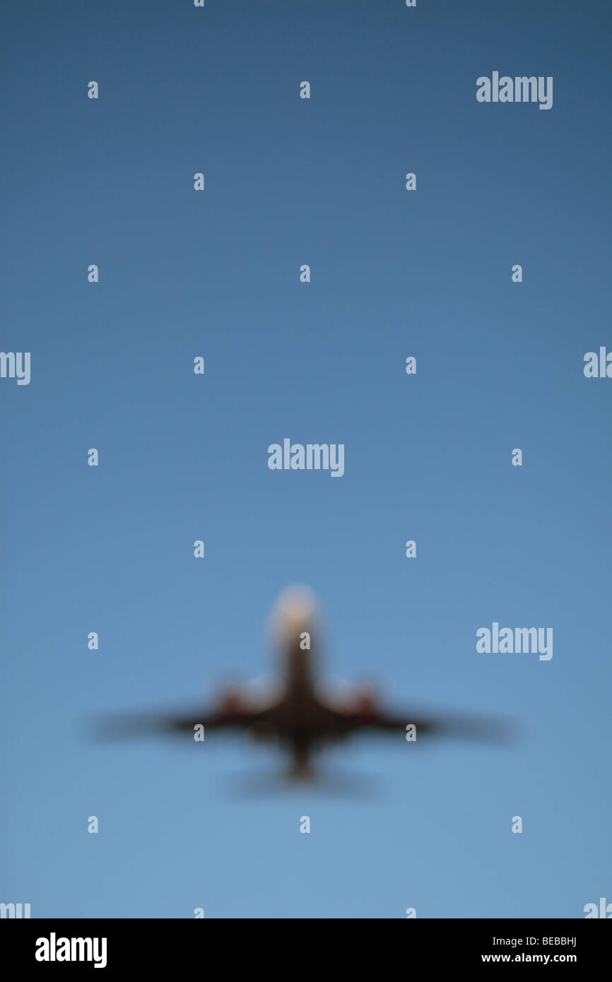 An out of focus image of a plane coming in to land on the South Runway at London's Heathrow Airport, UK. - Stock Image