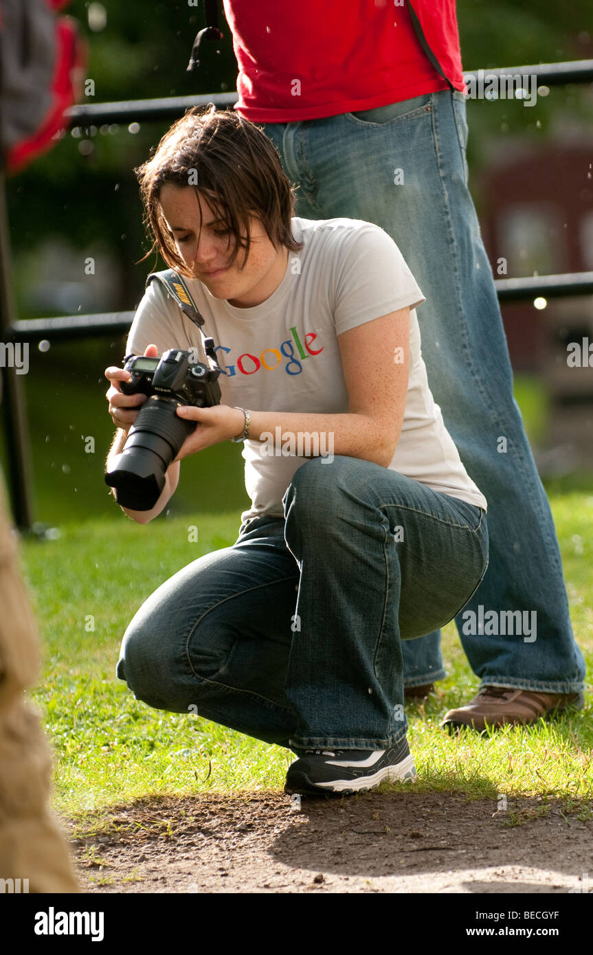 A young female photographer reviews images during a downpour. - Stock Image