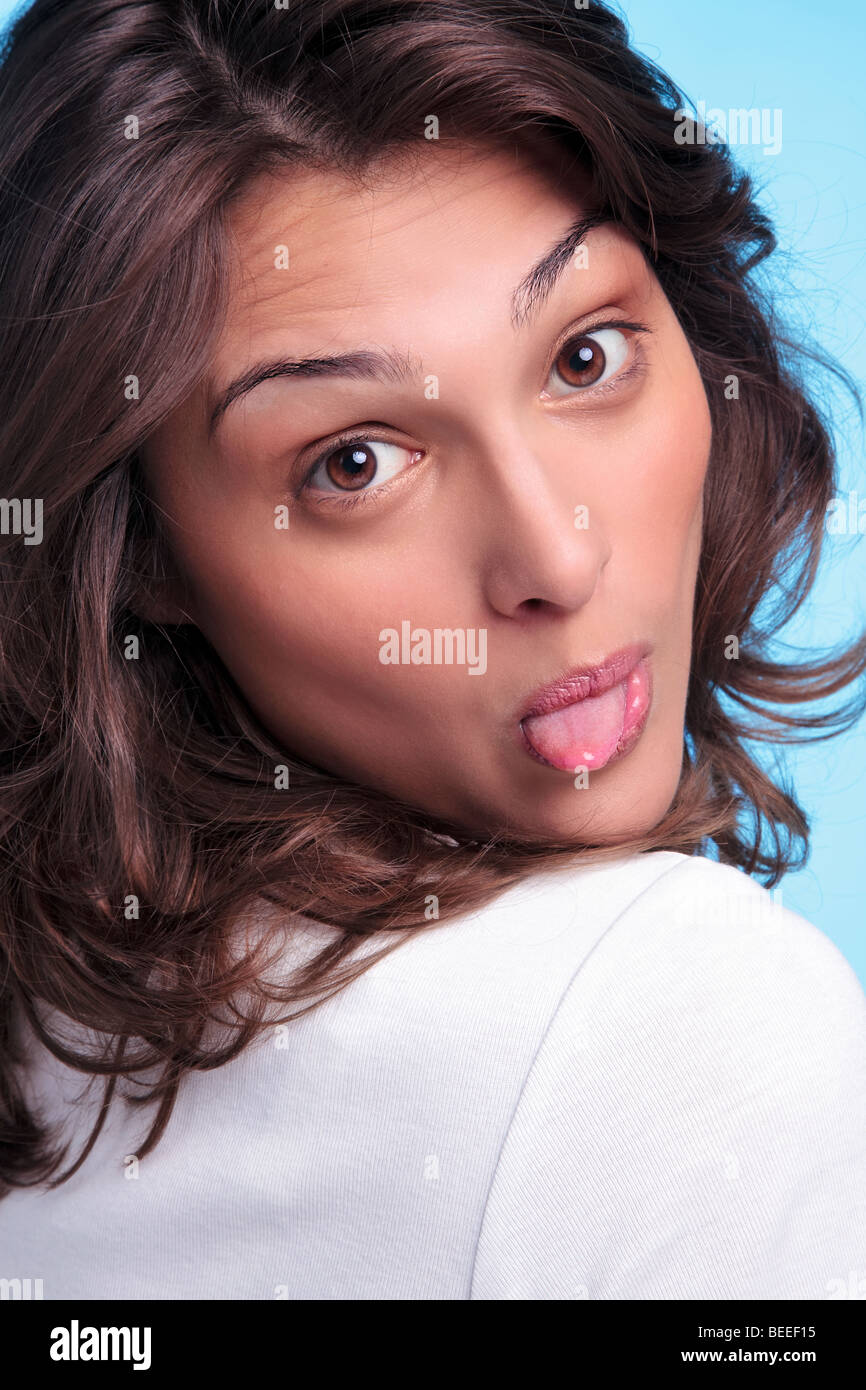 Cheeky brunette woman sticking her tongue out - Stock Image