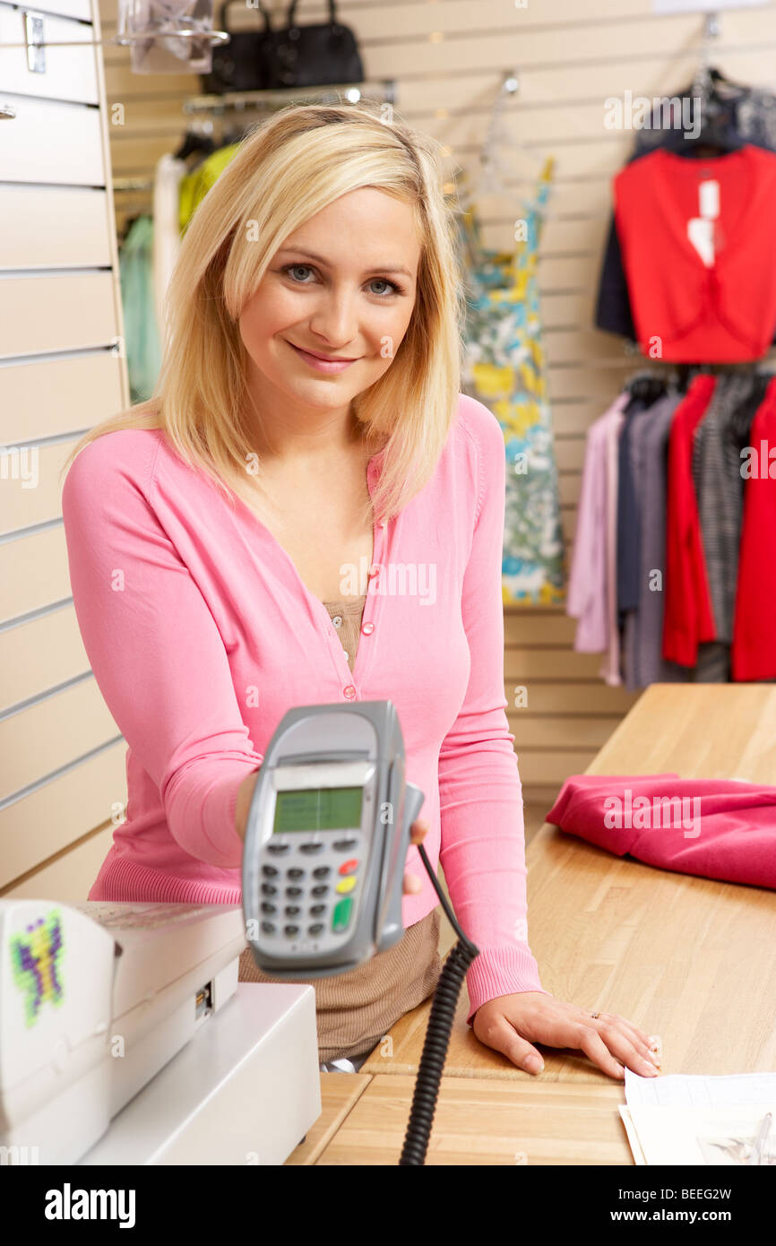 Female sales assistant in clothing store - Stock Image