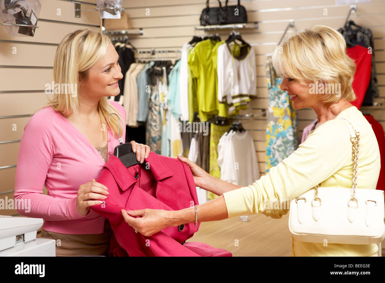 Sales assistant with customer in clothing store - Stock Image