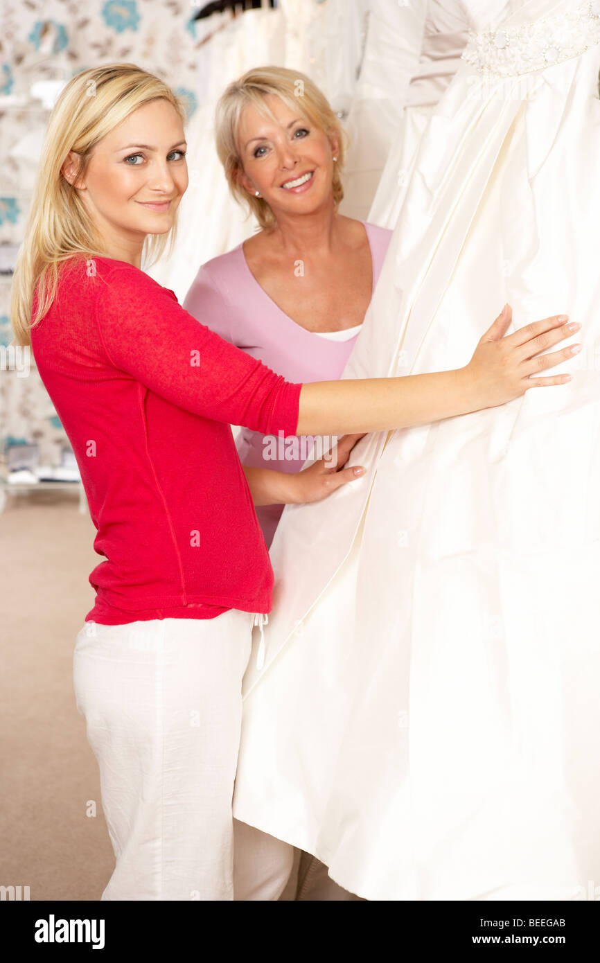 Bride trying on wedding dress with sales assistant - Stock Image