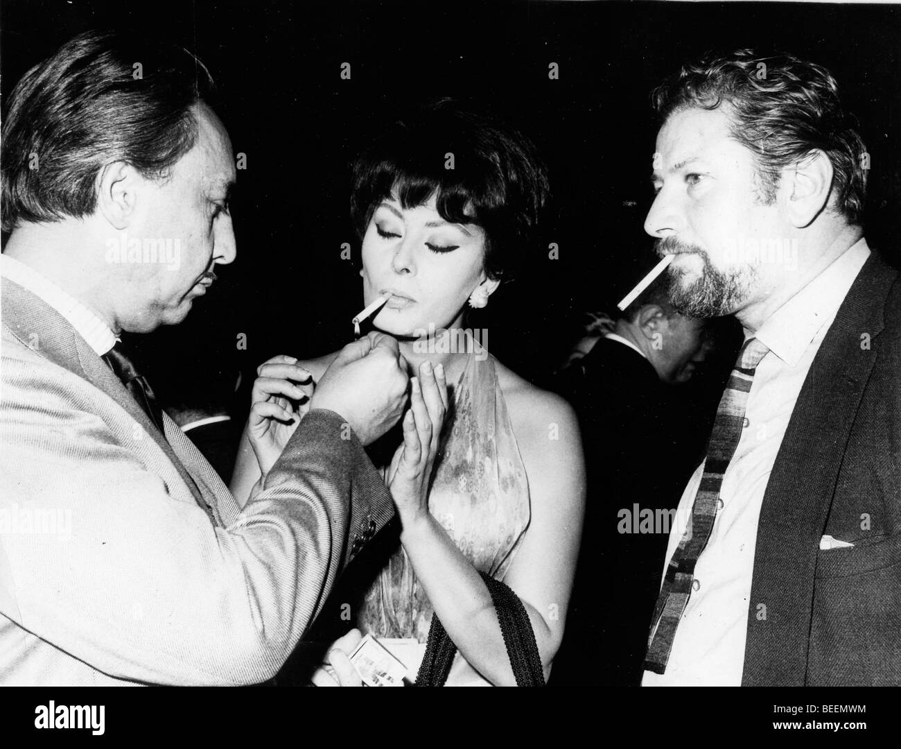 Actress Sophia Loren getting a light from Romain Gary with Peter Ustinov Stock Photo