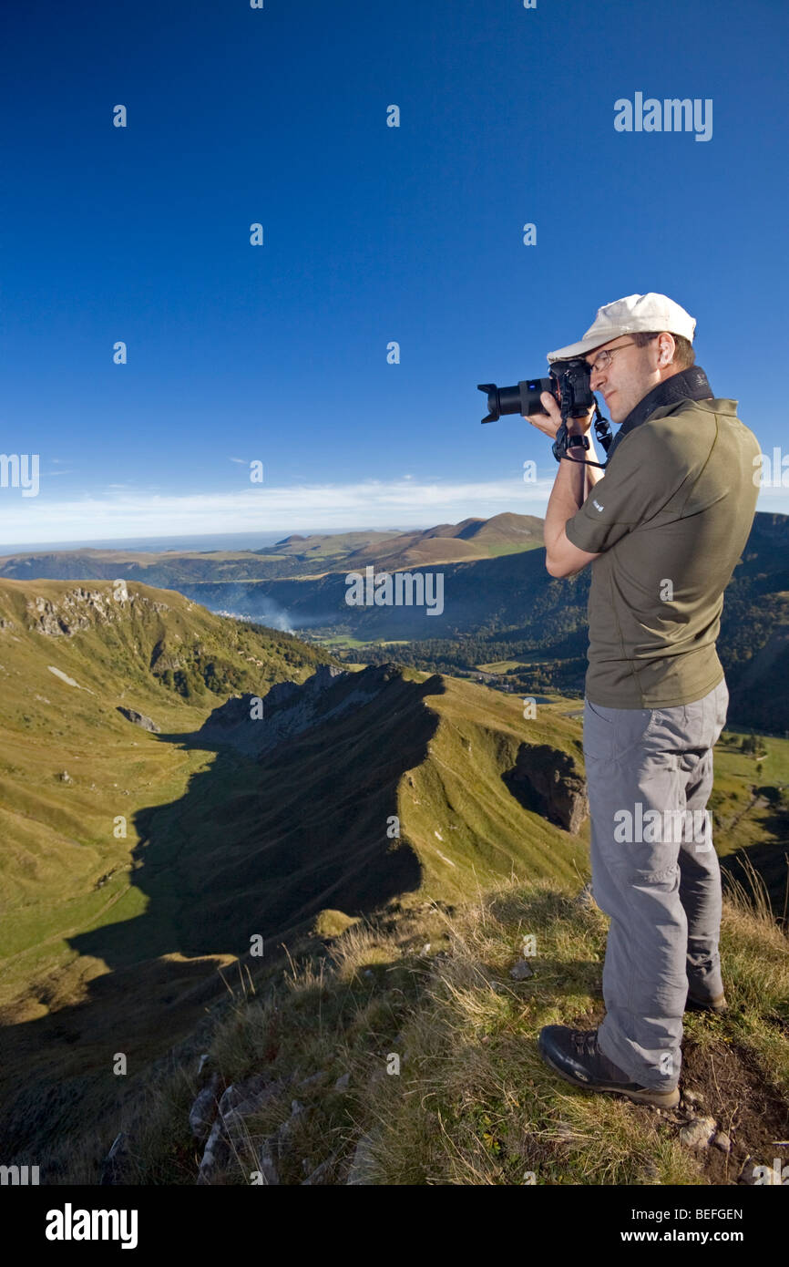 A hiker photographing the 'Val de Courre' in the Sancy Massif (Puy de Dôme France). Randonneur photographiant - Stock Image