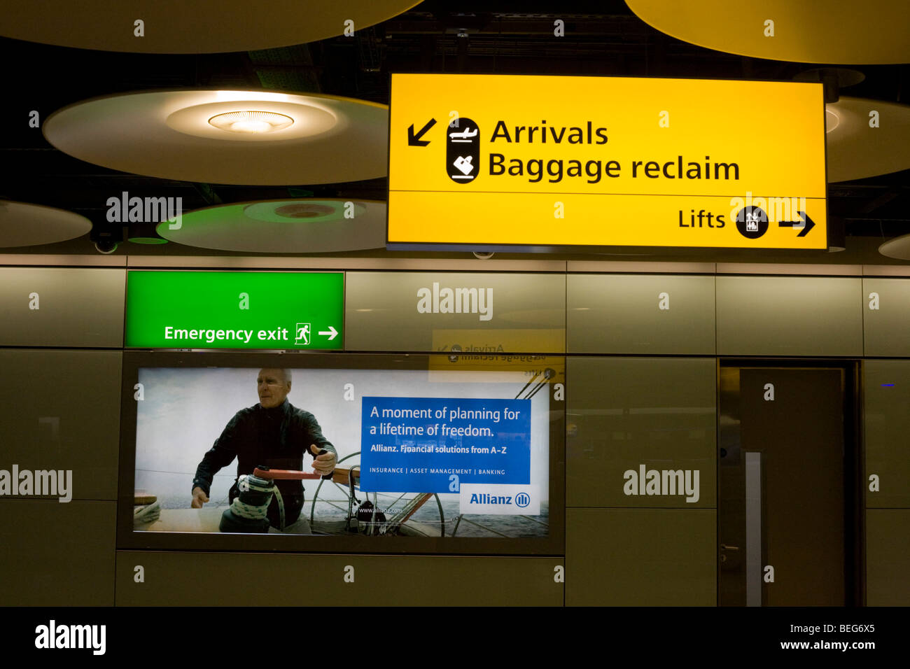 Baggage reclaim hall architecture and advertising at Heathrow's Terminal 5. - Stock Image
