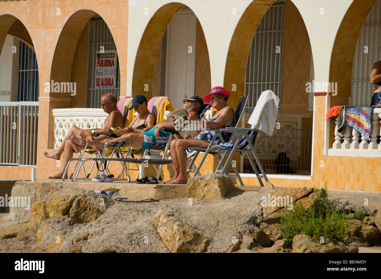 Two Elderly Couples Relaxing In The Sun On Beach Chairs Stock Photo ...