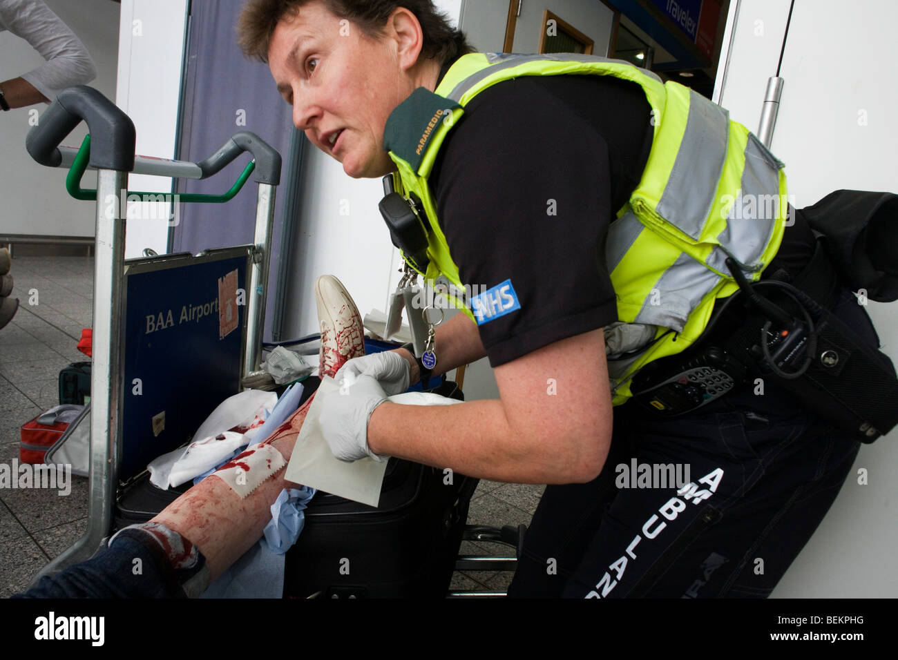 A female paramedic helps a lady passenger in Heathrow airport's terminal 3 who has tripped on escalators, badly - Stock Image