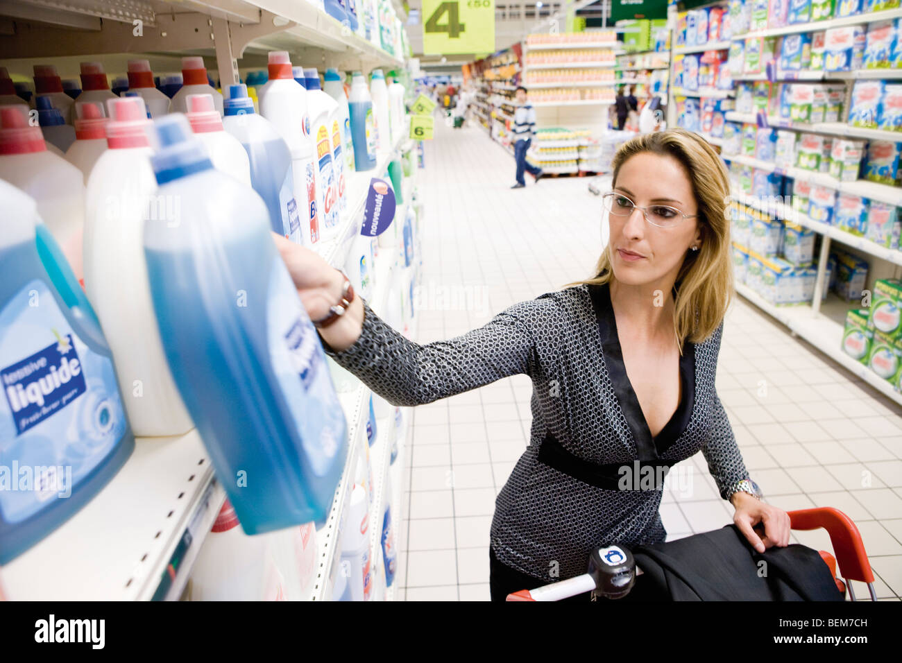Woman selecting bottle of detergent from supermarket shelf - Stock Image