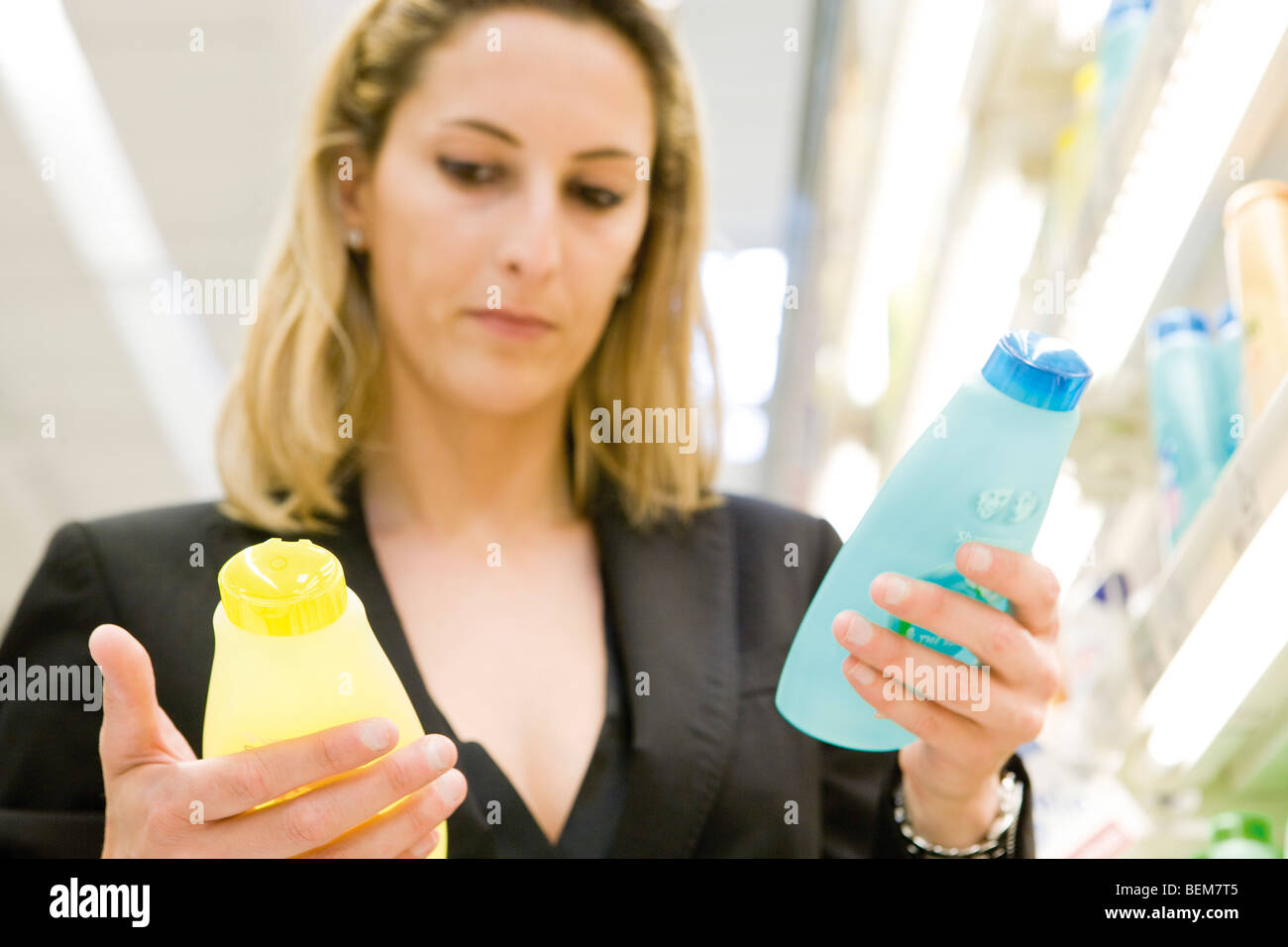 Woman comparing body care products - Stock Image