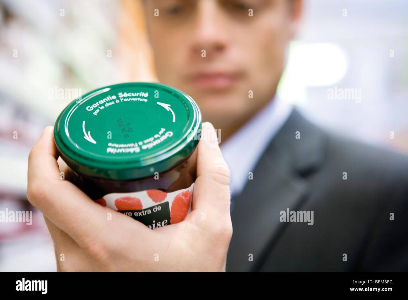 Man reading label on jar of jam - Stock Image