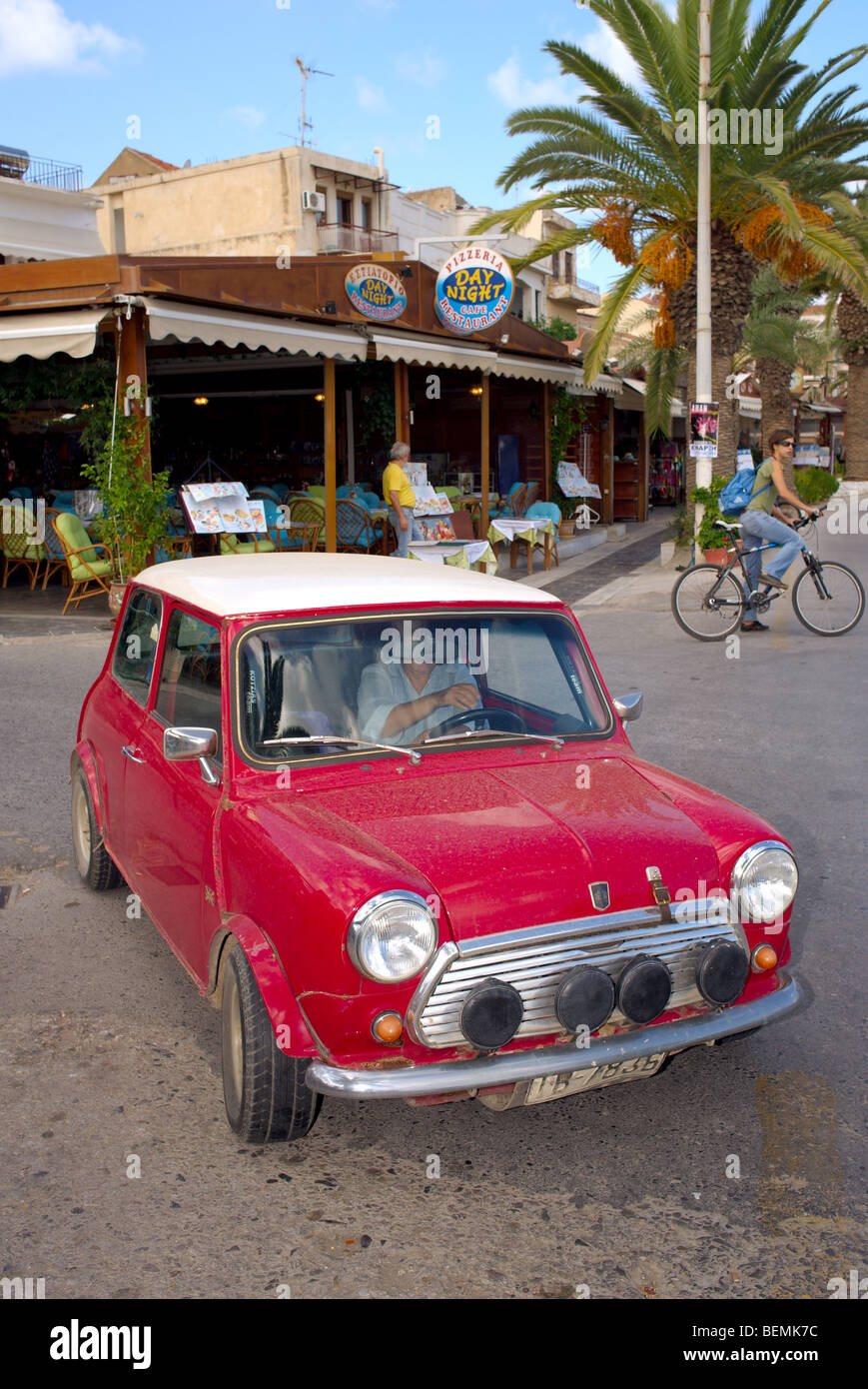 Classic red mini with white roof outside taverna and cyclist in distance Rethymnon Crete Greece - Stock Image