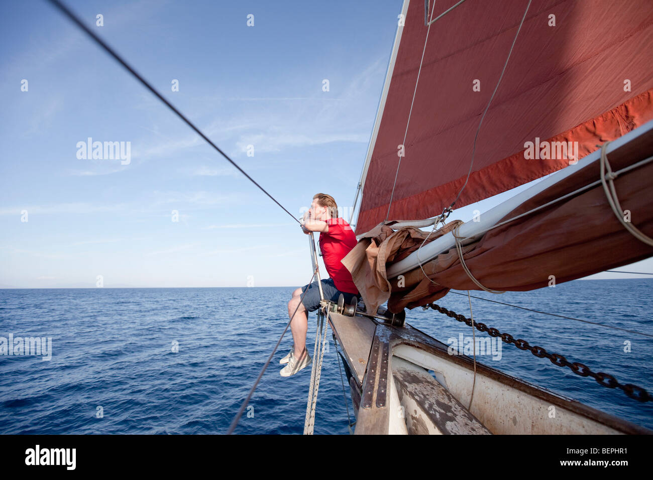 Man sitting at the bow of a ship - Stock Image