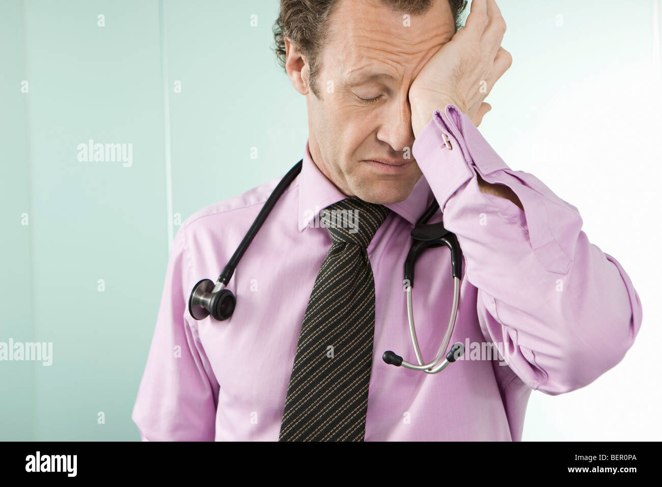 A tired doctor rubbing his eyes - Stock Image