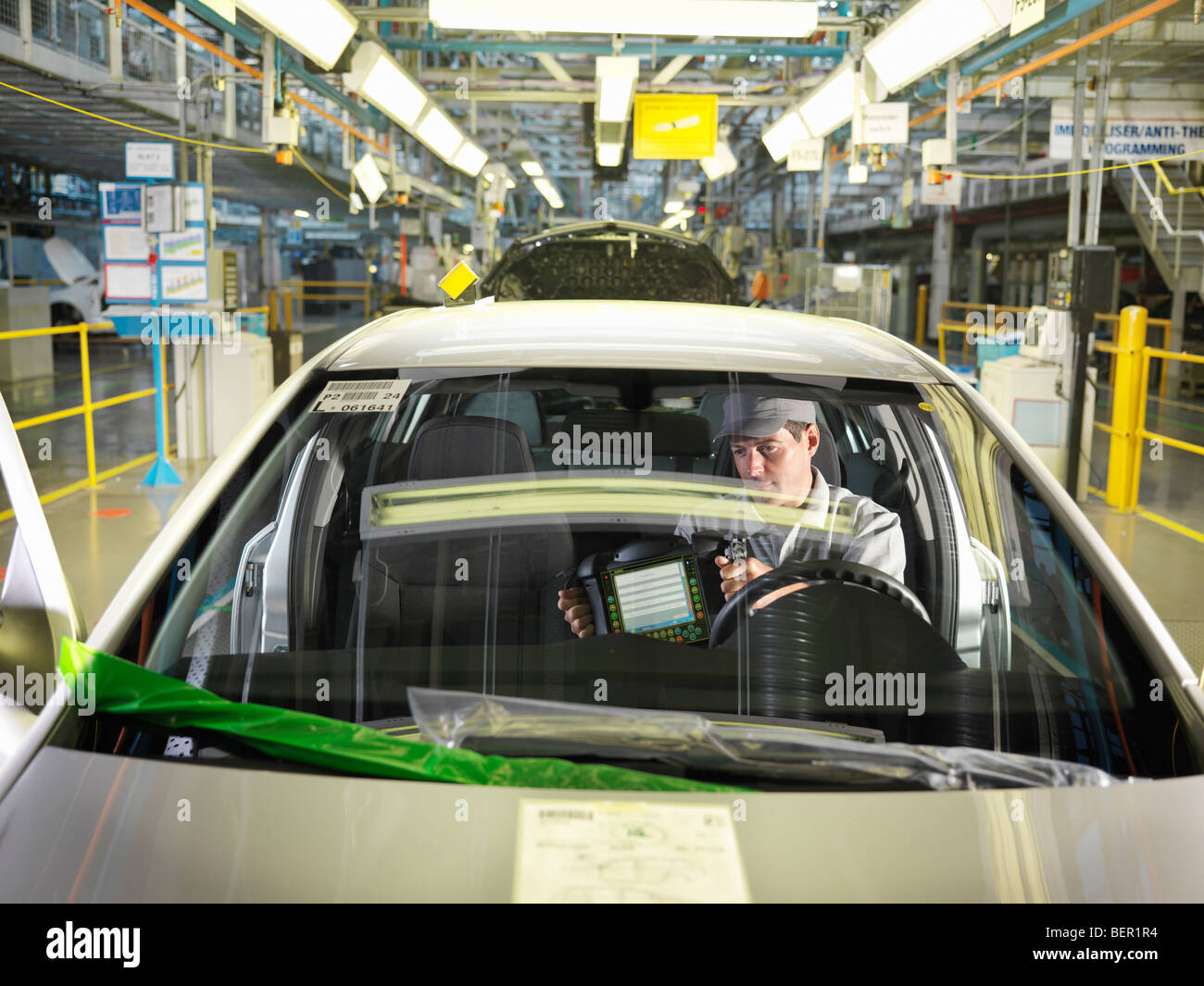 Car Worker In Car On Production Line - Stock Image