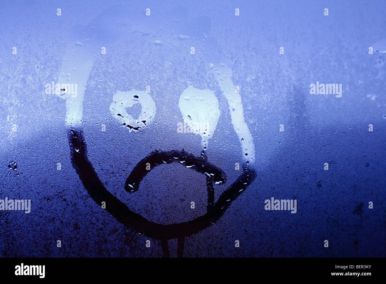 An unhappy childlike face drawn onto window condensation. - Stock Image