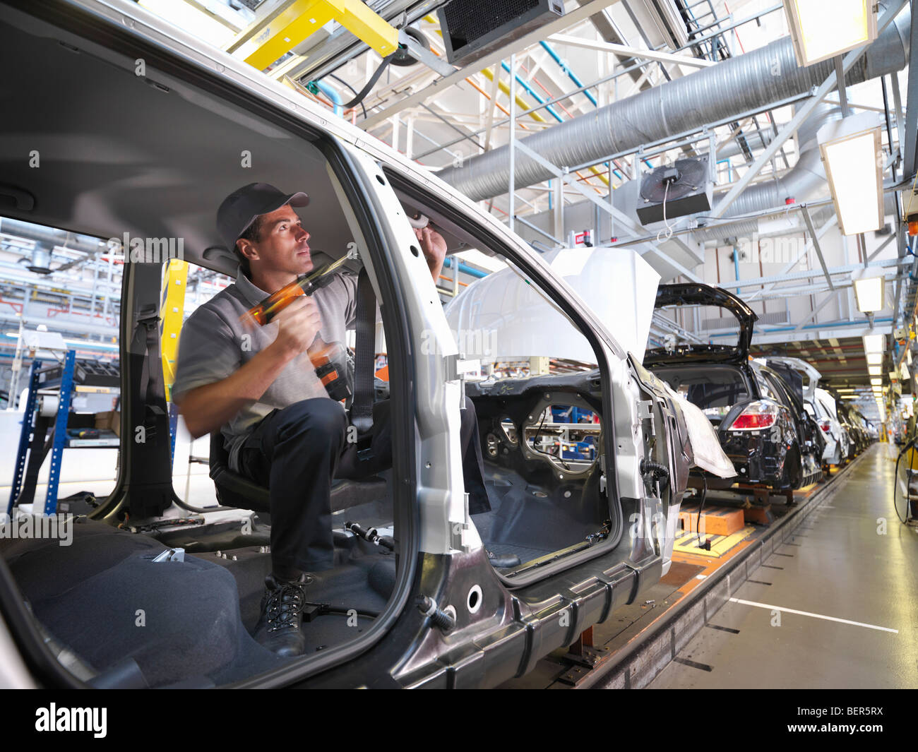 Car Plant Worker On Production Line - Stock Image