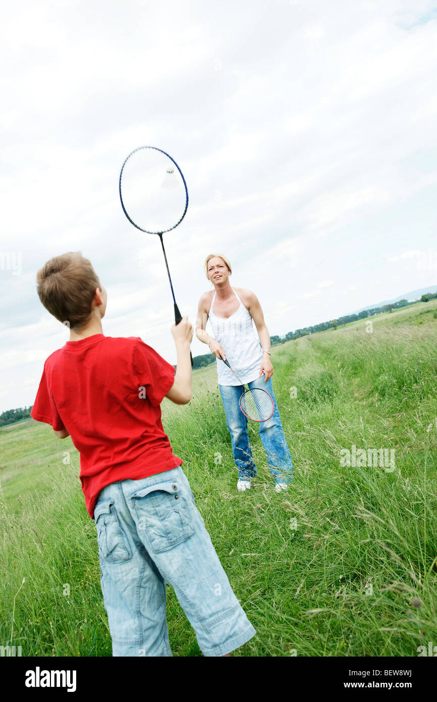 Mother and son playing badminton on a meadow - Stock Image