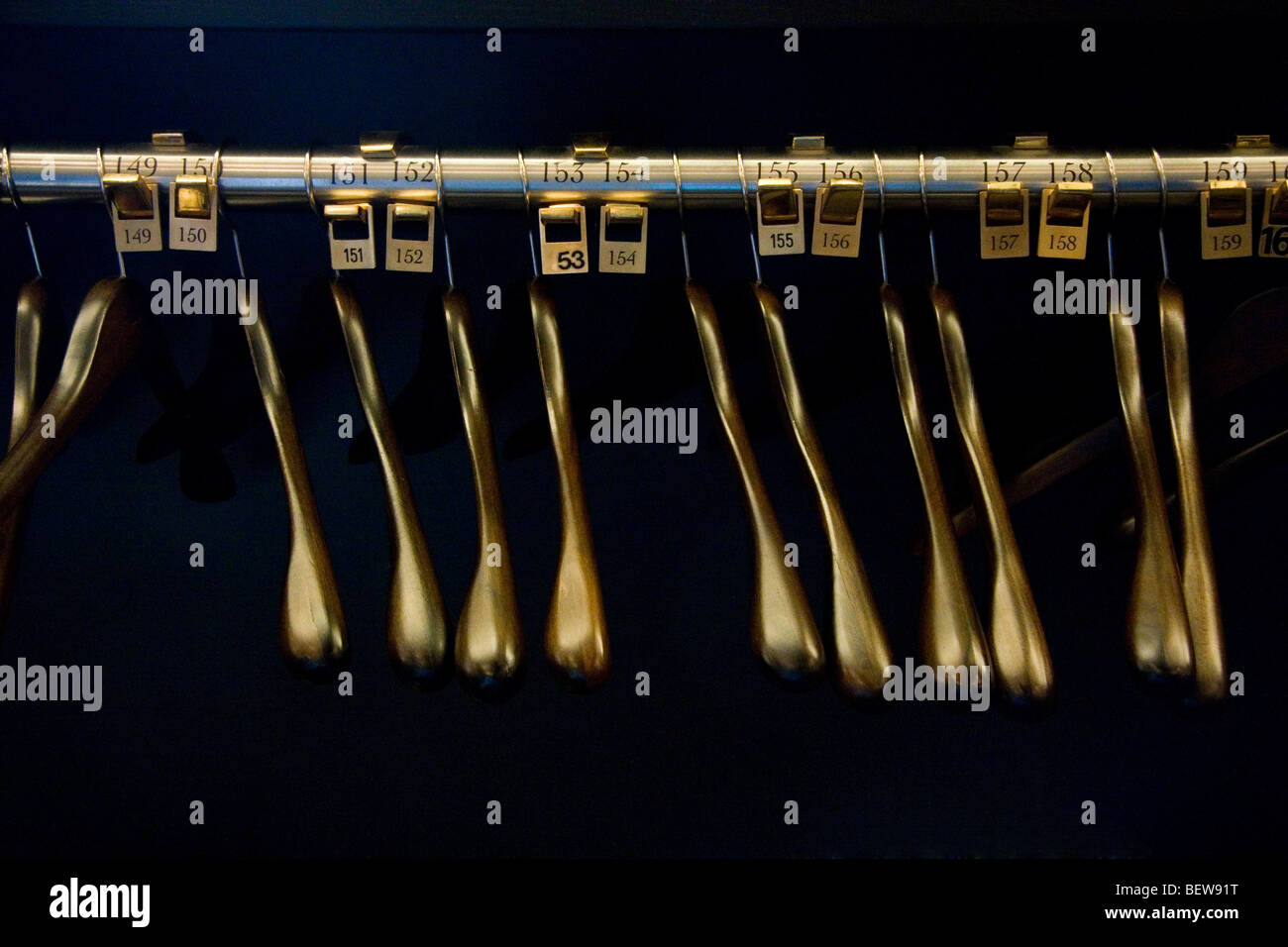 Clothes rail with golden empty hangers, close-up - Stock Image