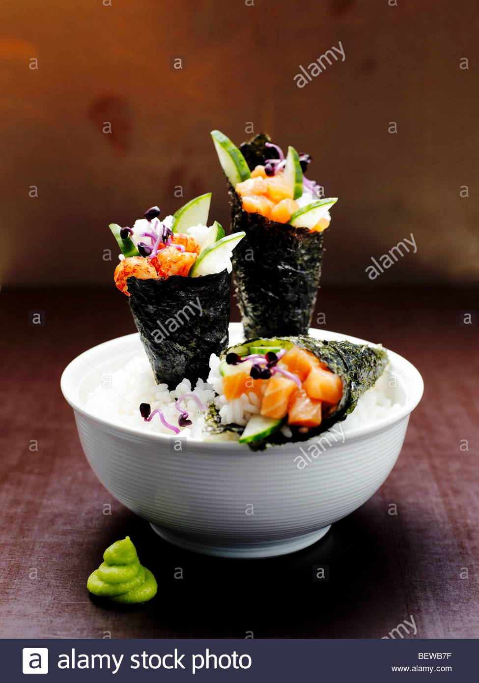 Three Temaki Sushi rolls in a rice bowl, close-up - Stock Image