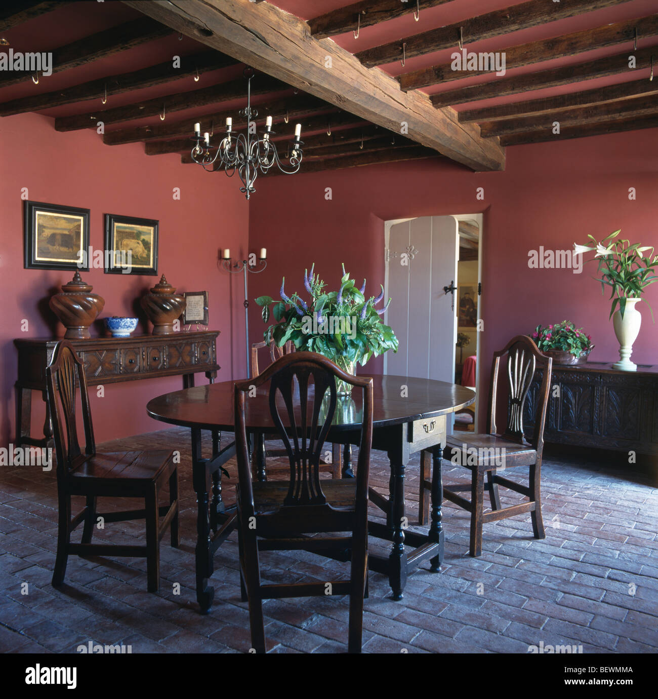 Antique oak table and chairs in red country dining room with brick antique oak table and chairs in red country dining room with brick flooring and rustic wooden ceiling beams dzzzfo