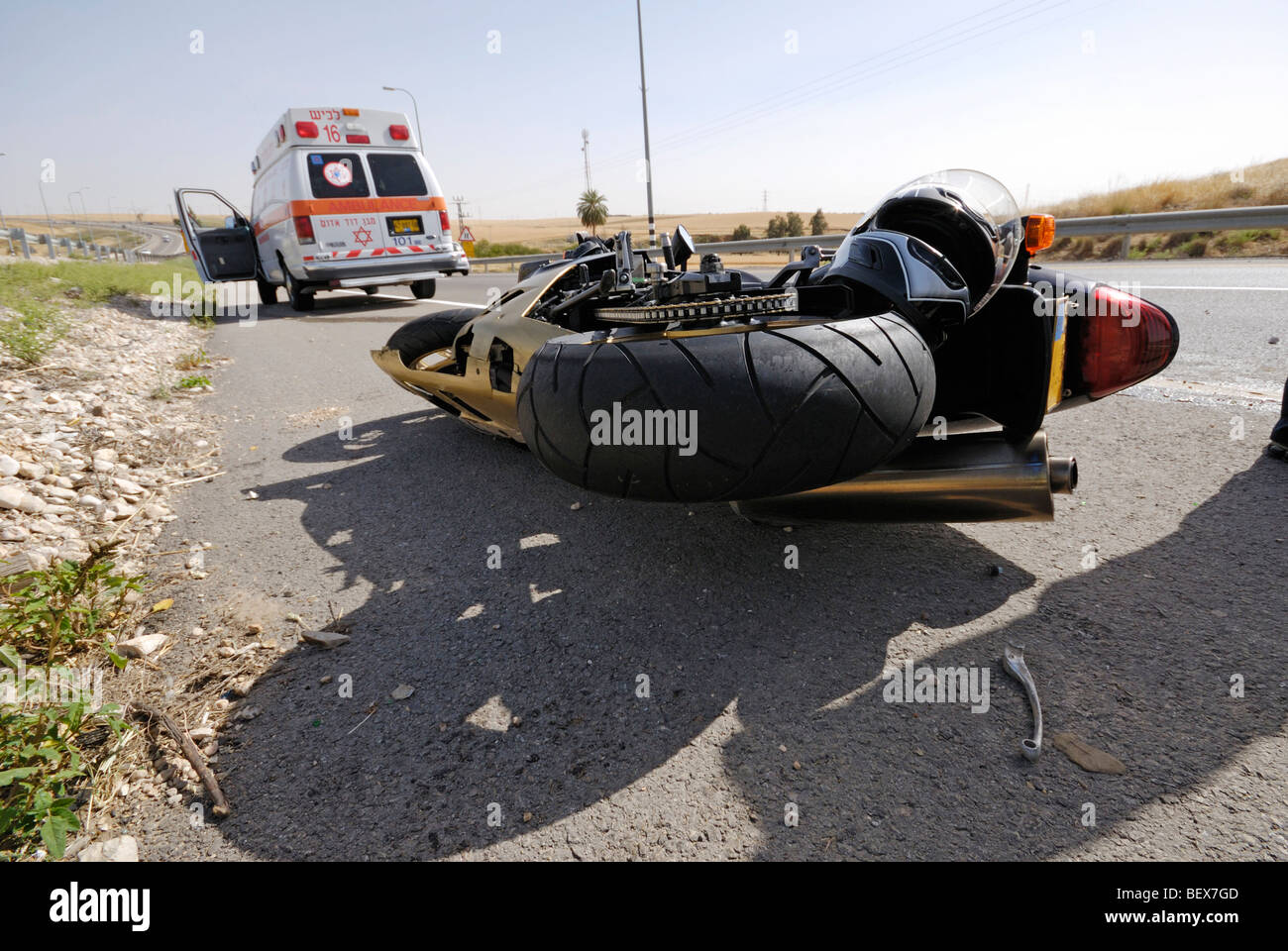 Israel, A motorbike lies on the road after a traffic collision Ambulance in the background - Stock Image
