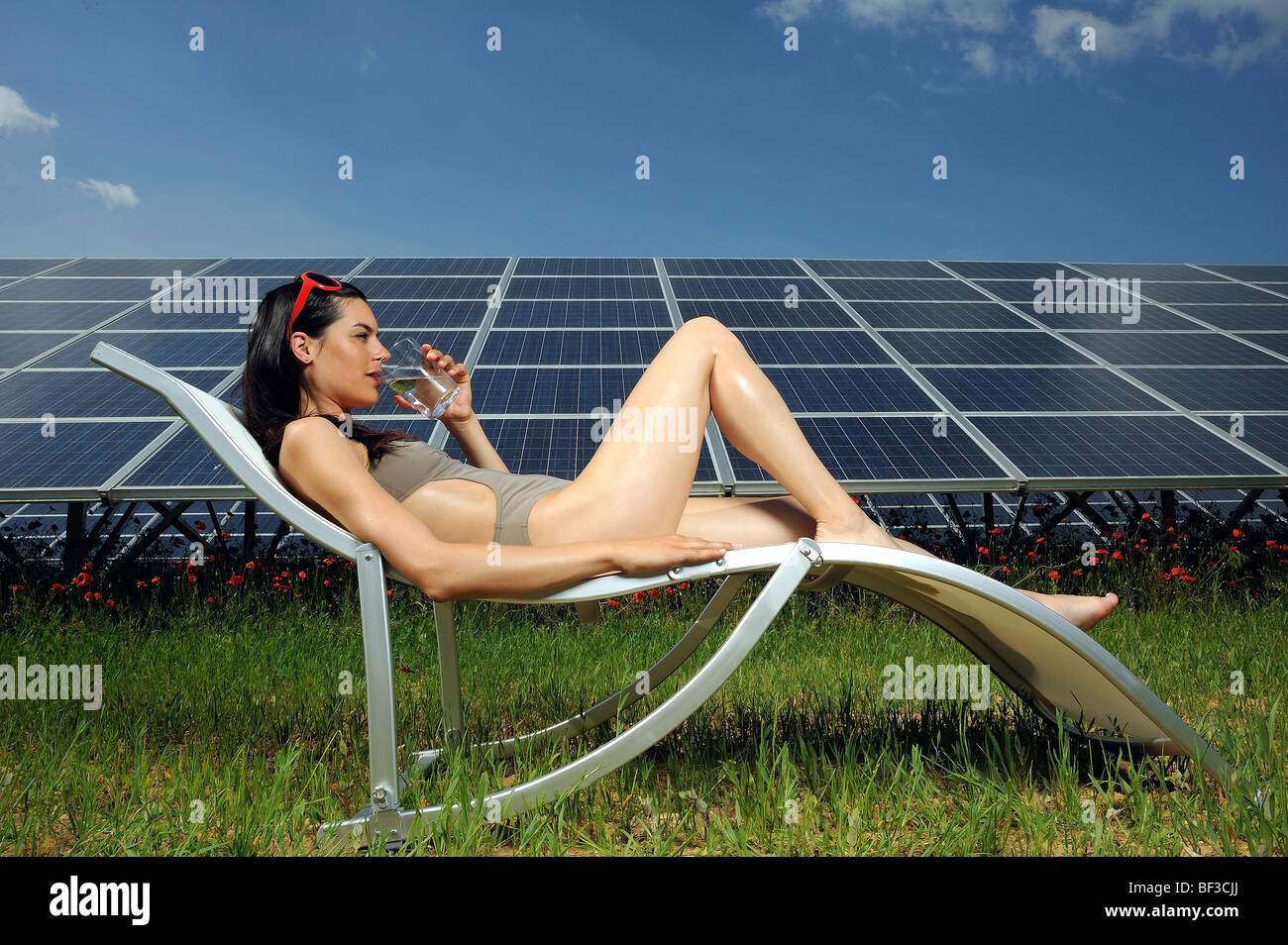 woman sunbathing in front of solar panel - Stock Image