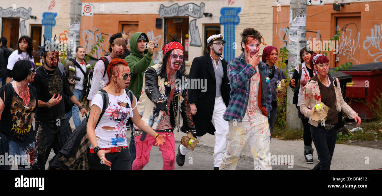 Panorama of a mob of Zombies with fake blood marching and lurching along in the annual Toronto Zombie walk - Stock Image
