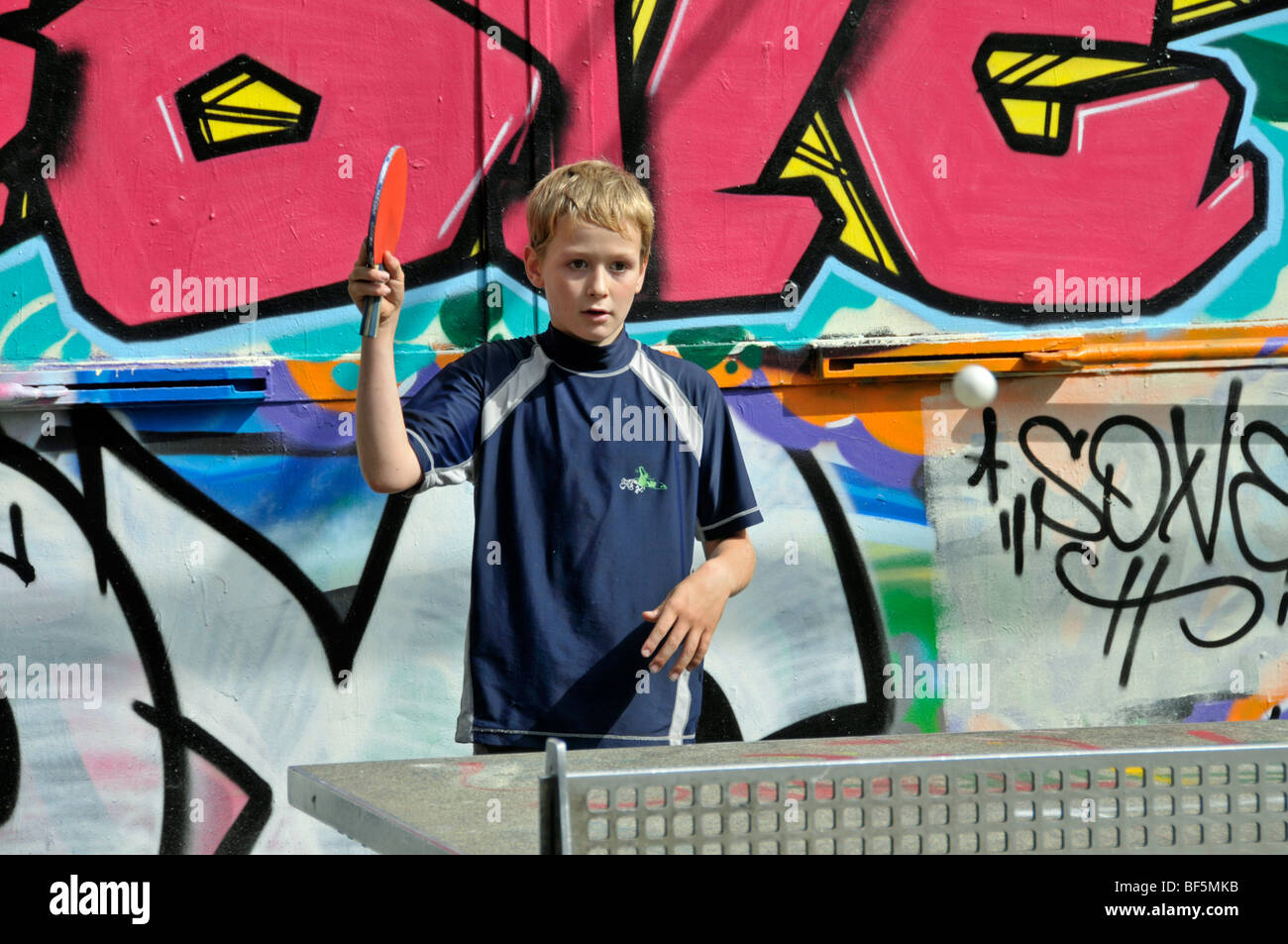 9-year-old boy playing table tennis, football ground in Cologne, North Rhine-Westphalia, Germany, Europe - Stock Image