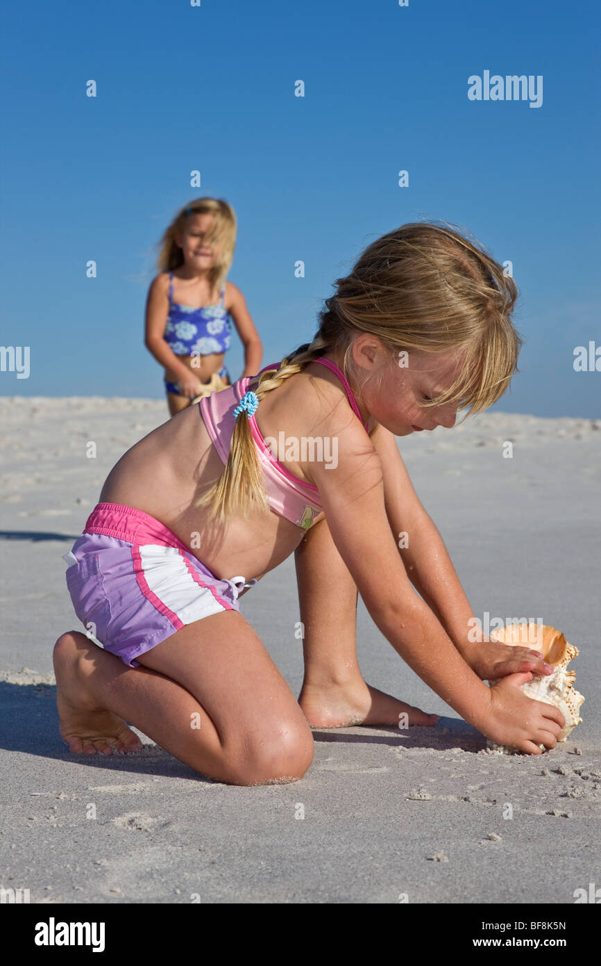 Two sisters wearing swimming costumes playing with shells on the beach.Cape Town South Africa - Stock Image