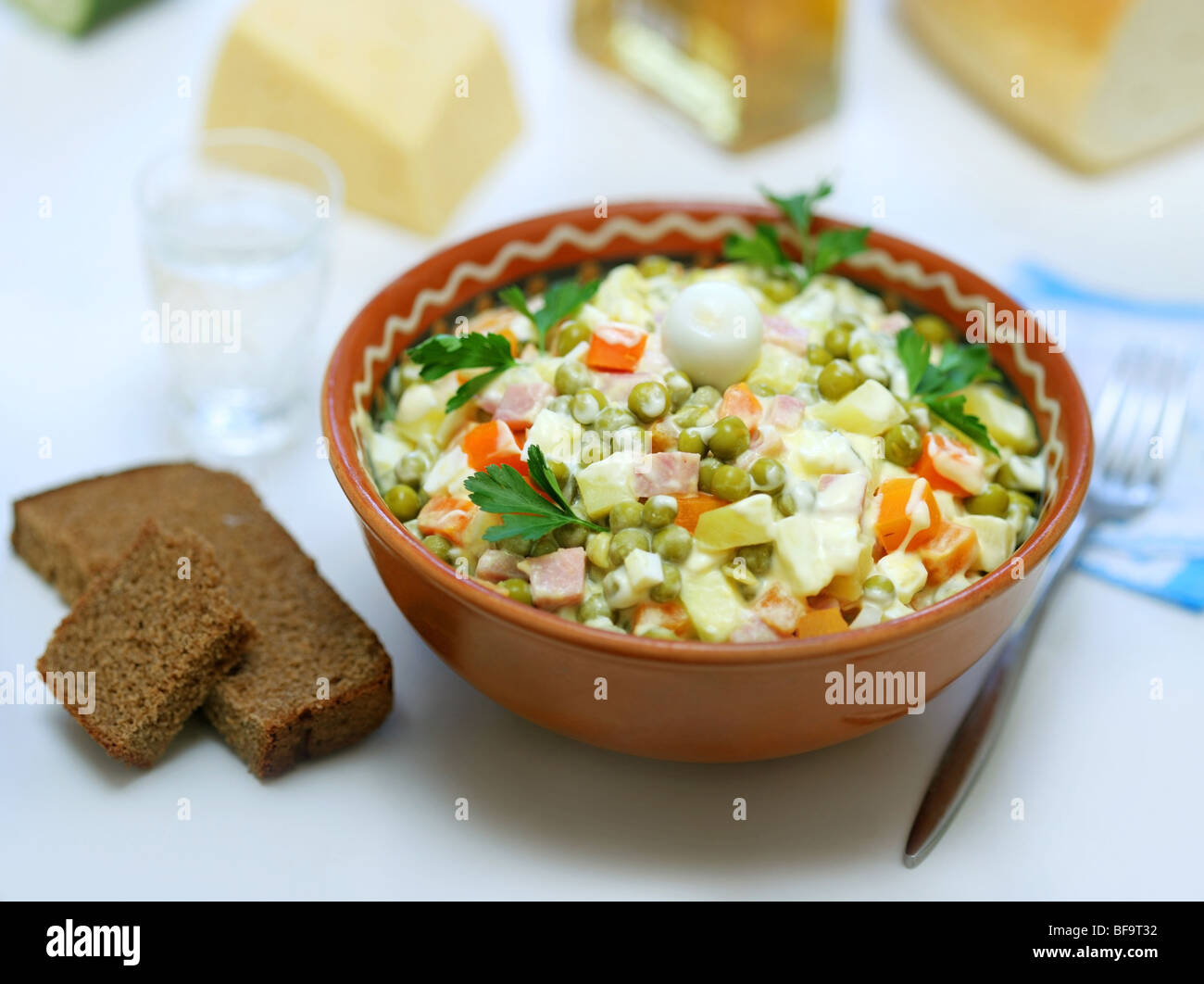Homemade variant of Russian Salad and pieces of bread near - Stock Image