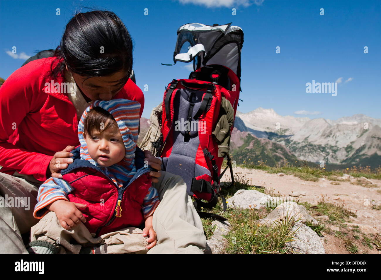 Mother kisses, plays with 14 month old son. Top of Buckskin Pass (12,462ft) Backpacking trip in Maroon Bells Snowmass - Stock Image
