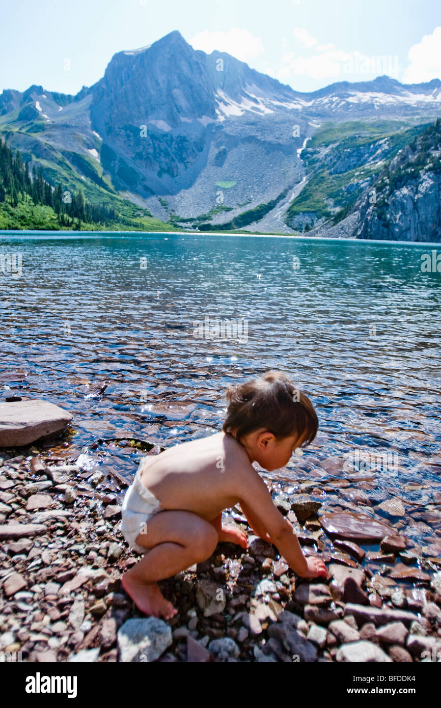 A 14 month boy plays in the waters of Snowmass Lake (10,980ft) with Snowmass Mountains in the background. - Stock Image